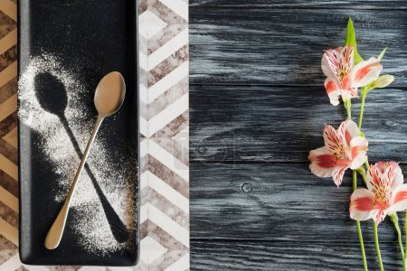top view of spoon with powder ready for dessert and beautiful flowers on wooden table