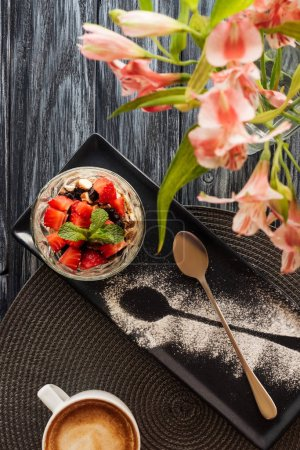 Photo for Top view of delicious fruity dessert in glass and flowers on wooden table - Royalty Free Image