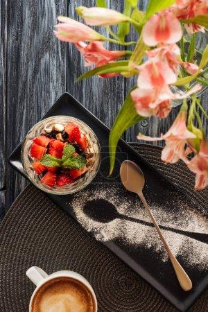 Photo pour Vue du dessus de délicieux dessert fruité en verre et fleurs sur table en bois - image libre de droit