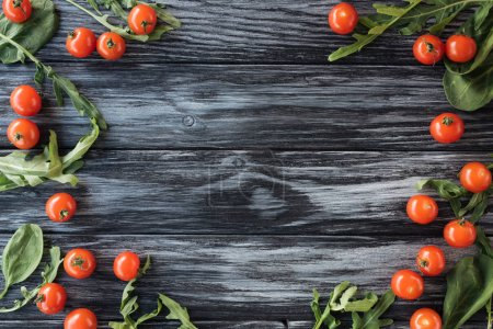 top view of fresh ripe tomatoes and arugula on wooden table with copy space