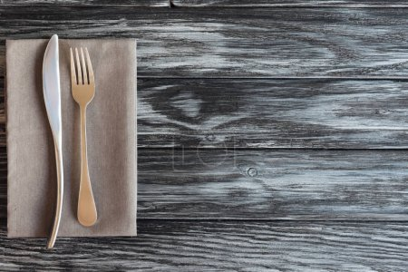 top view of fork and knife on napkin on wooden table