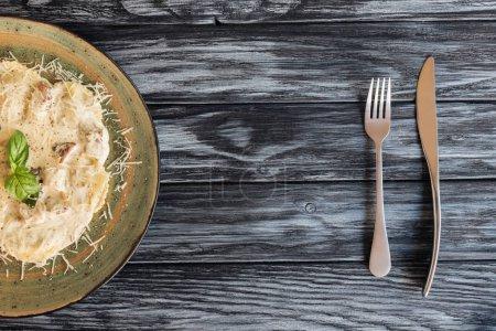 Photo pour Délicieux ravioli au fromage ricotta et épinards, des fourchettes et des couteaux sur la table en bois - image libre de droit
