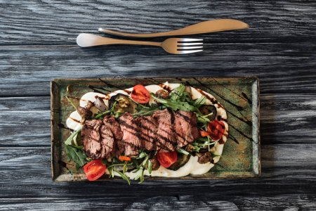 top view of gourmet sliced New York steak, vegetables and fork with knife on wooden table