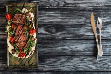 top view of delicious roasted steak with vegetables and fork with knife on wooden table