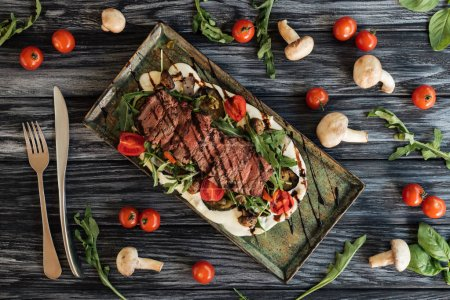 top view of delicious roasted steak, fork with knife and vegetables on wooden table
