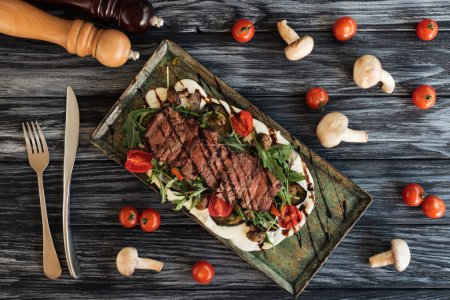 top view of delicious cooked steak with vegetables, fork with knife and spices on wooden table