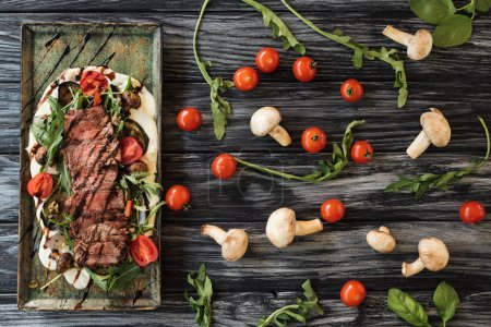 top view of delicious sliced cooked steak with vegetables on wooden table