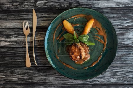 delicious cooked meat with sauce and basil leaves on plate, fork and knife on wooden table