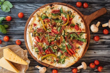 Blick von oben auf leckere Pizza mit Gemüse und Fleisch auf einem Holzschneidebrett