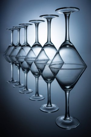 row of transparent martini glasses on grey with reflections