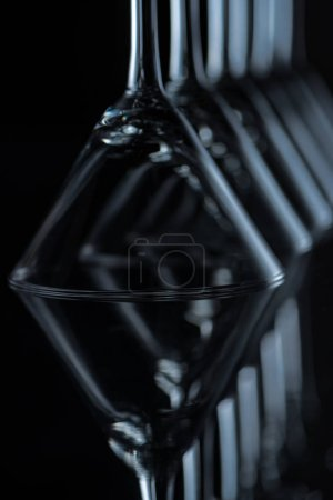 close up of martini glasses on black with reflections