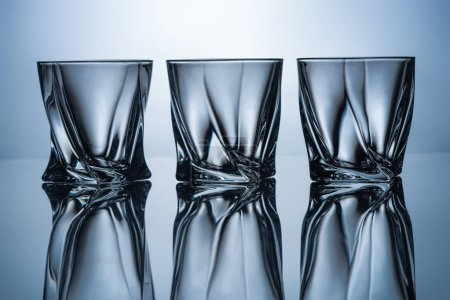 Photo for Row of three empty whiskey glasses on grey with reflections - Royalty Free Image