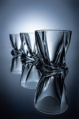 row of three cognac glasses on grey with reflections