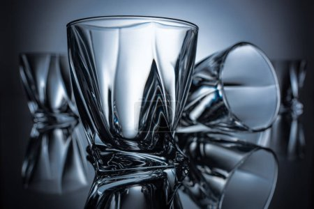 close up of cognac glasses on grey with reflections