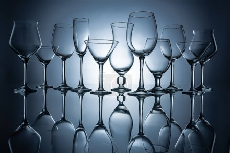 silhouettes of different empty glasses with reflections, on grey