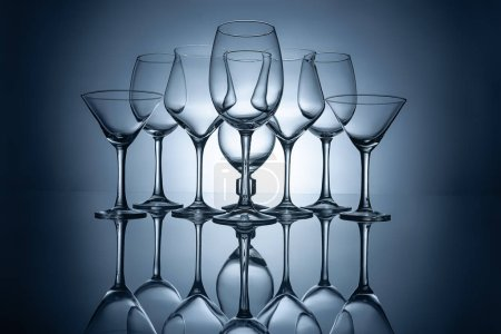 Photo for Different empty wine glasses with reflections, on grey - Royalty Free Image