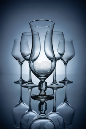 silhouettes of different empty wine glasses with reflections, on grey