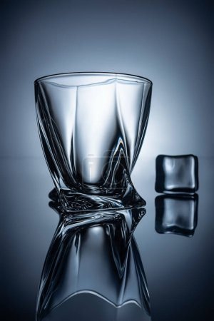 silhouettes of empty whiskey glass and ice cube, on grey