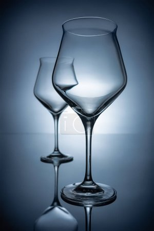 two empty transparent wine glasses on grey with reflections