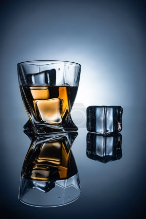 glass with cognac and ice cubes with reflections, on dark grey background