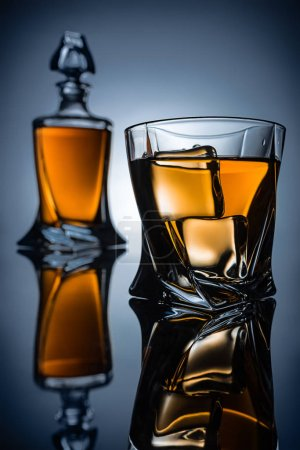 selective focus of bottle and glass with whiskey and ice cubes, on grey
