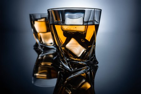selective focus of two glasses of cognac with ice cubes, on dark grey background