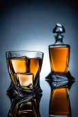 selective focus of whiskey glass with ice cubes and bottle, on grey