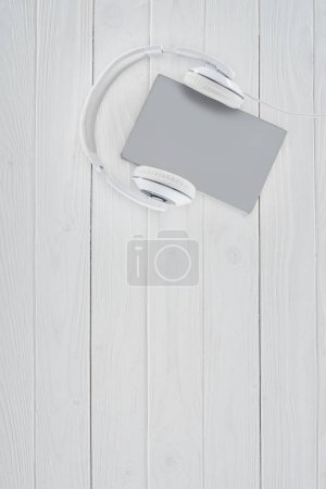 top view of grey book and headphones on white tabletop