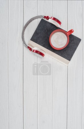 top view of book, headphones and red cup on white tabletop