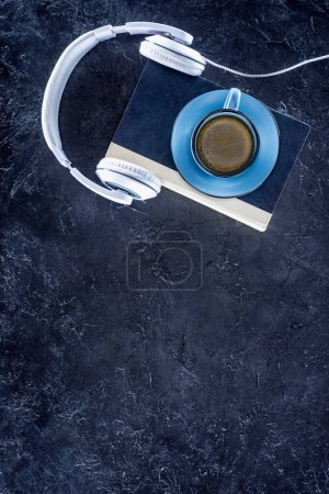 top view of book, headphones and blue cup with coffee on grey tabletop