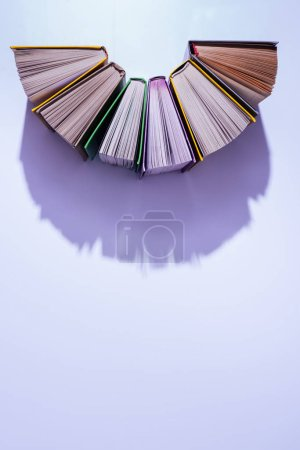 top view of stack of books in half circle on violet table