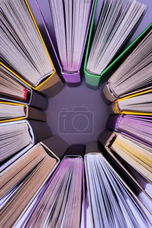 top view of stack of colored books in circle on violet table
