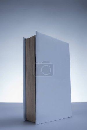 one white book on grey tabletop