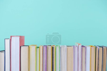row of different colored books isolated on blue