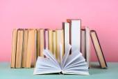 "Постер, картина, фотообои ""Откройте книгу перед рядок книг на столе на розовый"""