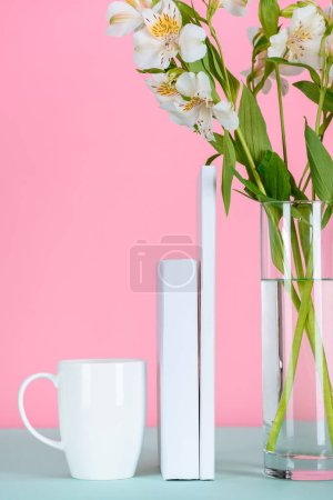 Photo for White books, cup on coffee and flowers in glass on table on pink - Royalty Free Image
