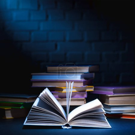 Photo for Open book in front of stack of colored books on dark surface - Royalty Free Image