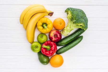 Photo pour Vue de dessus du symbole du coeur faite de fruits et légumes sur la surface en bois - image libre de droit
