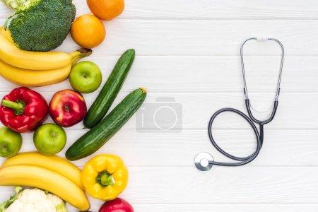Photo pour Vue de dessus de fruits frais avec les légumes et le stéthoscope sur la surface en bois - image libre de droit