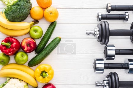 top view of fresh fruits with vegetables and various dumbbells on wooden surface