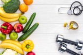 top view of fresh fruits and vegetables, dumbbells, stethoscope and measuring tape on wooden tabletop