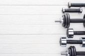 top view of dumbbells of various sizes on white wooden surface