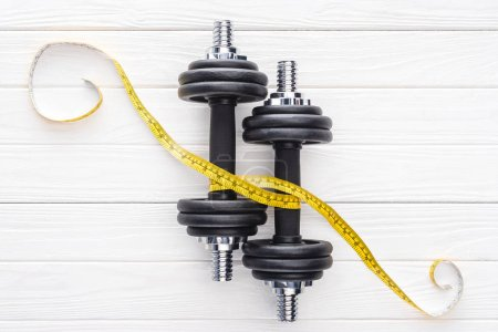 top view of dumbbells and yellow measuring tape on wooden surface