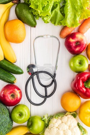 top view of fresh fruits and vegetables and stethoscope on wooden table