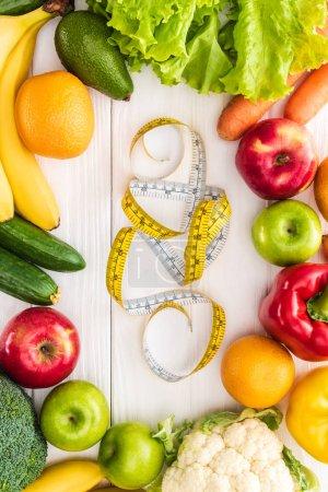 Draufsicht auf frisches Obst und Gemüse und Maßband auf Holztisch