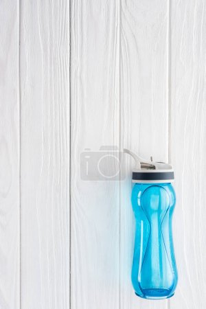 top view of blue sports bottle with water on white wooden table