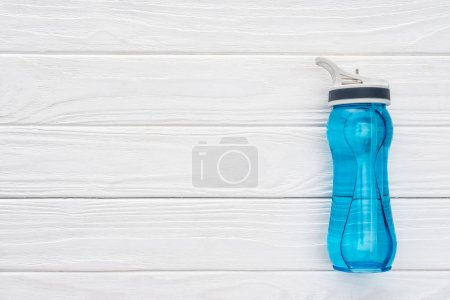 top view of blue sports bottle with water on white wooden surface