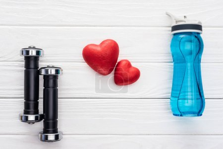 top view of dumbbells, bottle of water and red hearts on wooden surface