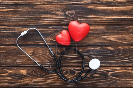 Photo for Top view of stethoscope and red hearts symbol on wooden table - Royalty Free Image