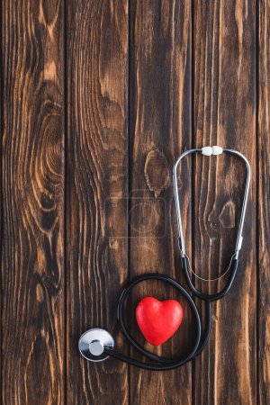 top view of stethoscope and red heart symbol on wooden table